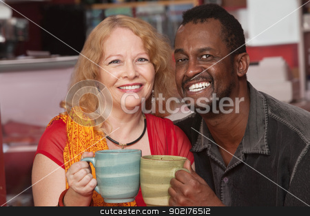 Smilng Middle Aged Couple stock photo, Smiling middle aged husband and wife holding coffee mugs by Scott Griessel
