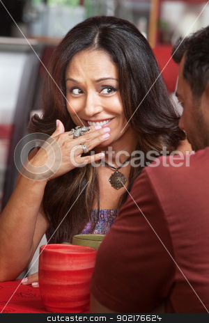 Embarrassed Lady Smiling stock photo, Bashful Hispanic woman across from friend smiling by Scott Griessel