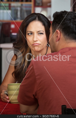 Frowning Woman Looking at Man stock photo, Doubtful woman looking at man sitting in cafe by Scott Griessel
