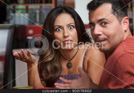 Annoyed Couple in Cafe stock photo, Annoyed Latino male and female looking over in cafe by Scott Griessel