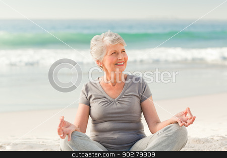 Senior woman practicing yoga on the beach stock photo, Senior woman practicing yoga on the beach by Wavebreak Media