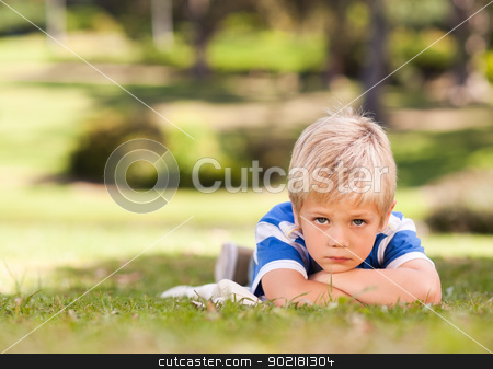 Boy lying down in the park stock photo, Boy lying down in the park by Wavebreak Media