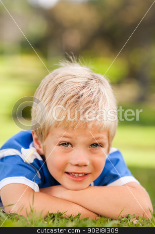 Boy lying down in the park stock photo, Boy lying down in the park by Wavebreak Media