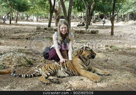 Tourist girl and Tiger stock photo, Caucasian young woman and the Tiger in a Tiger Temple, Kanchanaburi province, Thailand by Yulia Zhukova