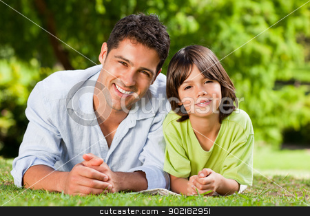 Father and his son lying down stock photo, Father and his son lying down by Wavebreak Media