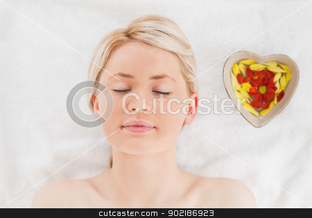 Young blonde woman lying down near flower petals stock photo, Young blonde woman lying down near flower petals in a Spa centre by Wavebreak Media