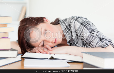 Good looking red-haired girl having a rest while studying for an stock photo, Good looking red-haired girl having a rest while studying for an examination at her desk by Wavebreak Media