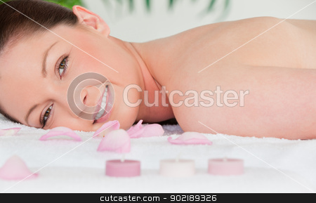 Smiling youn woman lying on her belly with petals and unlighted  stock photo, Smiling youn woman lying on her belly with petals and unlighted candles by Wavebreak Media