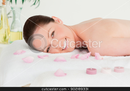 Smiling young woman lying on her belly with petals and unlighted stock photo, Smiling young woman lying on her belly with petals and unlighted candles by Wavebreak Media
