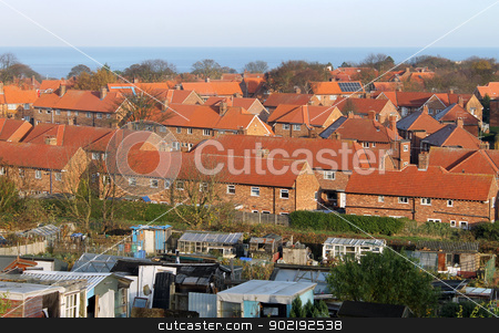Red brick housing estate in England stock photo, Traditional English red brick housing estate with allotment buildings in foreground, Scarborough, North Yorkshire, England. by Martin Crowdy
