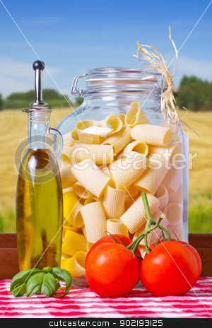 Pasta stock photo, Typical Italian pasta inside a glass jar, with tomatoes and basil by Fabio Alcini