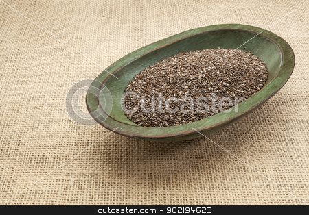 chia seed bowl stock photo, chia seeds in a rustic oval wood bowl against canvas by Marek Uliasz