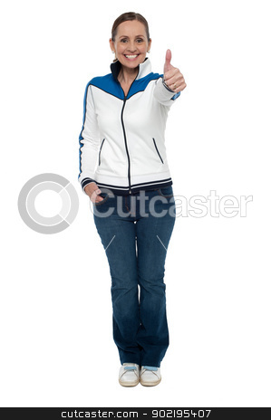 Casual charming woman gesturing thumbs up stock photo, Casual charming woman gesturing thumbs up. Full length studio shot. by Ishay Botbol