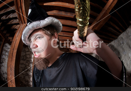 Wizard Holding Staff Over Shoulder stock photo, Menacing young Caucasian wizard with staff over his shoulder by Scott Griessel