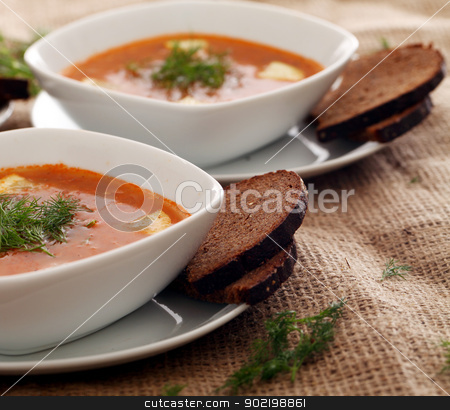 Soup served with bread on a beige tablecloth