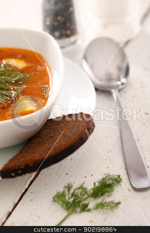 Bowl of red soup served with bread on table