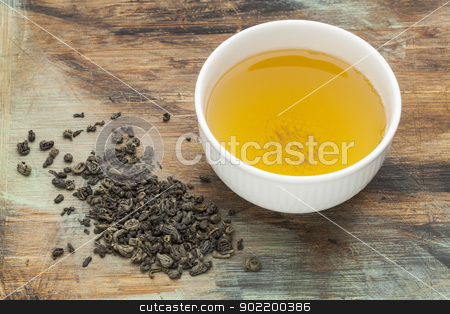 gunpowder green tea stock photo, gunpowder green tea - a white cup of drink and loose leaves on a grunge painted wood background by Marek Uliasz