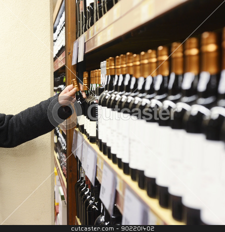Man Choosing Wine Bottle From Shelves In Store stock photo, Caucasian man in jacket choosing wine bottle from shelves in store by Corepics VOF