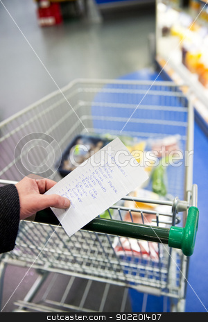 Shopping cart and groceries stock photo, Hand, holding a shopping list with day to day groceries and other necessities, whilst pushing a shopping cart through a supermarket by Corepics VOF