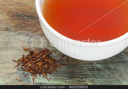 rooibos red tea stock photo, rooibos red tea  - a white cup of drink and loose leaves on wood background, tea made from the South African red bush, naturally caffeine free by Marek Uliasz