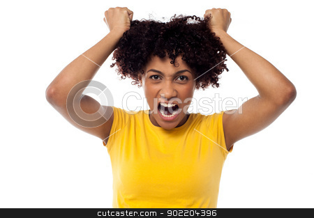 Angry young woman pulling her hair out stock photo, Irritated woman pulling her hair with both hands, screaming aloud. by Ishay Botbol