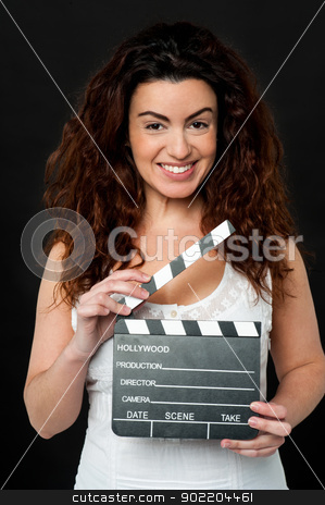 Get ready for the next shot, it's showtime stock photo, Stylish woman isolated on black background posing with clapperboard. by Ishay Botbol