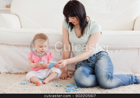 Pretty woman holding her baby in her arms while sitting on a car stock photo, Pretty woman holding her baby in her arms while sitting on a carpet in the living room by Wavebreak Media