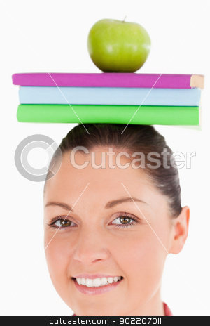 Beautiful female holding an apple and books on her head while st stock photo, Beautiful female holding an apple and books on her head while standing against a white background by Wavebreak Media