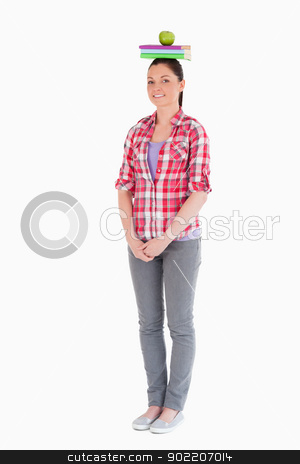 Charming female holding an apple and books on her head while sta stock photo, Charming female holding an apple and books on her head while standing against a white background by Wavebreak Media