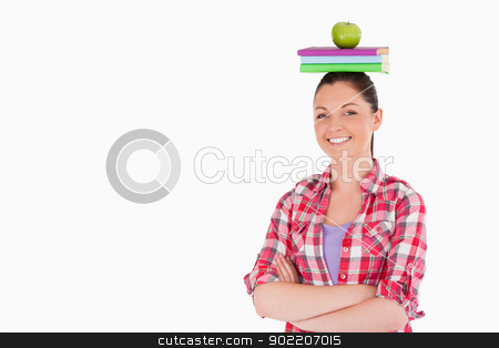 Pretty female holding an apple and books on her head while stand stock photo, Pretty female holding an apple and books on her head while standing against a white background by Wavebreak Media