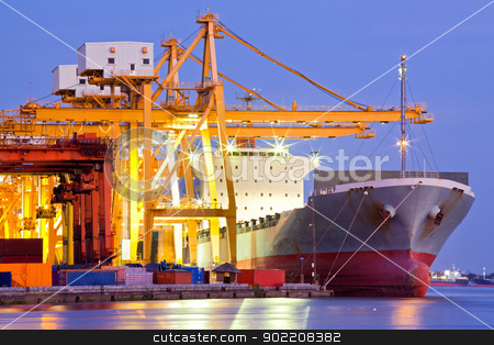 Industrial Container Cargo Ship stock photo, Industrial Container Cargo freight ship with working crane bridge in shipyard at dusk for Logistic Import Export background by Vichaya Kiatying-Angsulee