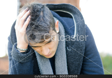 Desperate, sad or upset young man holding his head stock photo, Desperate, sad, worried or upset young man holding his head by Stefano Cavoretto