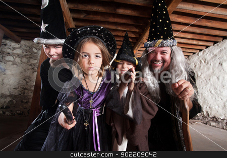 Spell Casting Family stock photo, Magician father and children casting spells in a basement by Scott Griessel