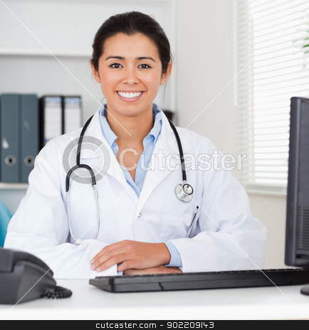 Beautiful woman doctor with a stethoscope posing stock photo, Beautiful woman doctor with a stethoscope posing in her office by Wavebreak Media