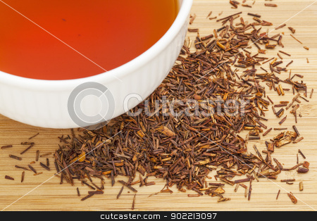 rooibos red tea  stock photo, rooibos red tea  -  a white cup of drink and loose leaves on bamboo wood background, tea made from the South African red bush, naturally caffeine free by Marek Uliasz