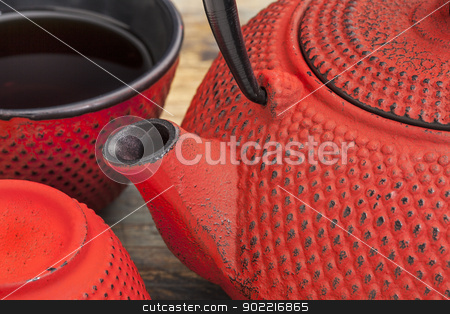red tetsubin with cups stock photo, red tetsubin with a cup of tea - a detail of a traditional cast iron Japenese teapot by Marek Uliasz