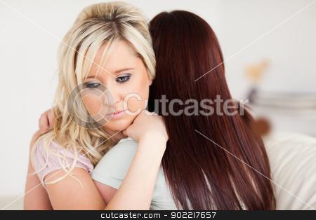 Young sad women hugging on a sofa stock photo, Young sad women hugging on a sofa in a living room by Wavebreak Media
