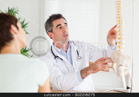 Doctor showing a woman a part of a spine stock photo, Doctor showing a woman a part of a spine in a room by Wavebreak Media