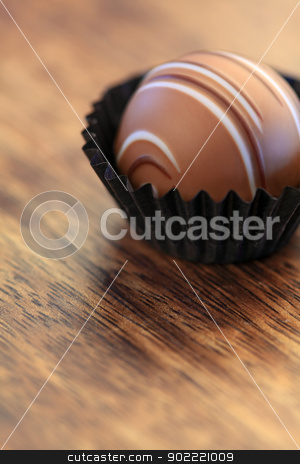 Praline in a paper wrapper stock photo, Photo with shallow depth of field, of a single praline in a paper wrapper sitting on a wood table. by &copy; Ron Sumners