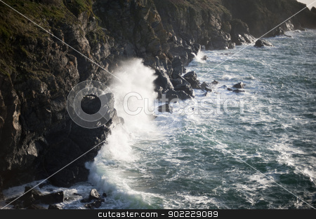 stormy ocean breaking wave stock photo, spray flying off a rock as a breaking wave crashes ashore on a rugded rock coastline by Stephen Gibson