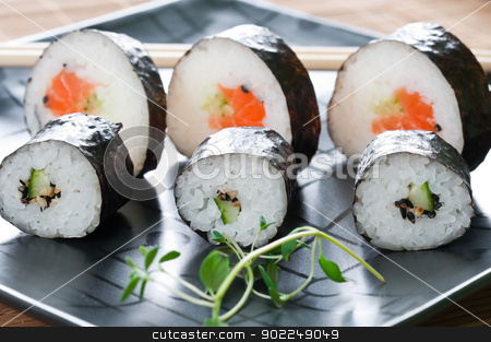 Japanese Sushi stock photo, Selection of Japanese sushi arranged with thyme on black plate by Tiramisu Studio