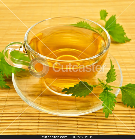 Herbal tea with nettles on a bamboo mat stock photo, Herbal tea in a glass cup and saucer, three twig nettle on a bamboo napkin by rezkrr