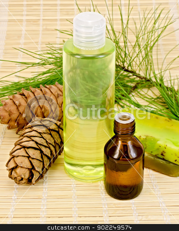 Oil and shower gel with cedar cones stock photo, Cedar oil in a bottle, cedar cones with branch, two green homemade soap, shower gel on a bamboo mat by rezkrr