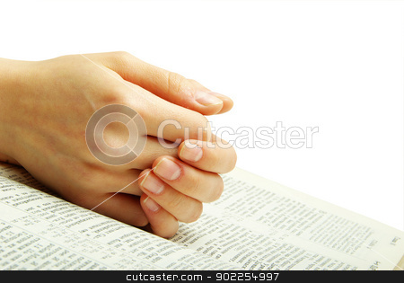 bible stock photo, hands clasped in prayer over a  Bible by Vitaliy Pakhnyushchyy