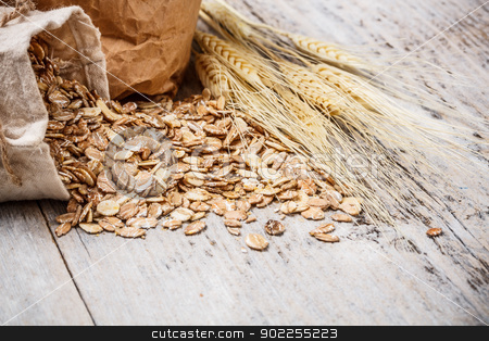 Oat flakes stock photo, Oat flakes spilling from the burlap bag on wooden table by Grafvision