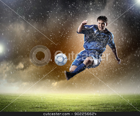 football player striking the ball stock photo, football player in blue shirt striking the ball aloft at the stadium under the rain by Sergey Nivens