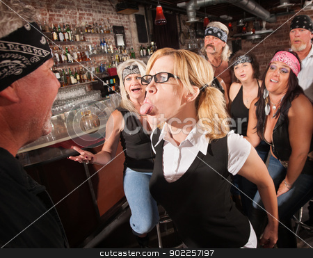 Nerd Sticking Out Tongue in Bar stock photo, Aggressive female nerd sticking her tongue out at gang member by Scott Griessel