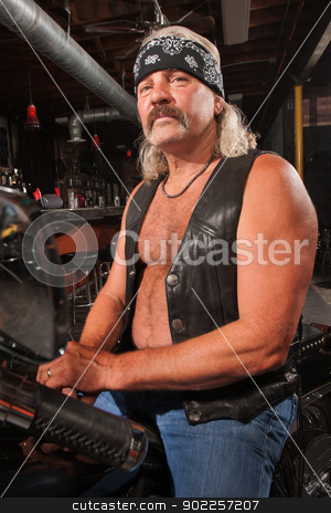 Biker Gang Man on Motorcycle stock photo, Tough middle aged man on motorcycle in bar by Scott Griessel
