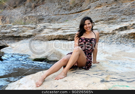 Young Hispanic Woman stock photo, Young Hispanic woman near a creek. by Henrik Lehnerer
