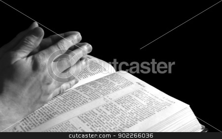 Bible stock photo, A mans hands clasped in prayer over a  Bible by Vitaliy Pakhnyushchyy